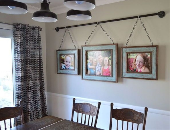 After building rustic picture frames out of some scrap lumber, we designed a unique way to hang them on our dining room wall. Iron pipe is affordable and easy to find, even at the local hardware store!
