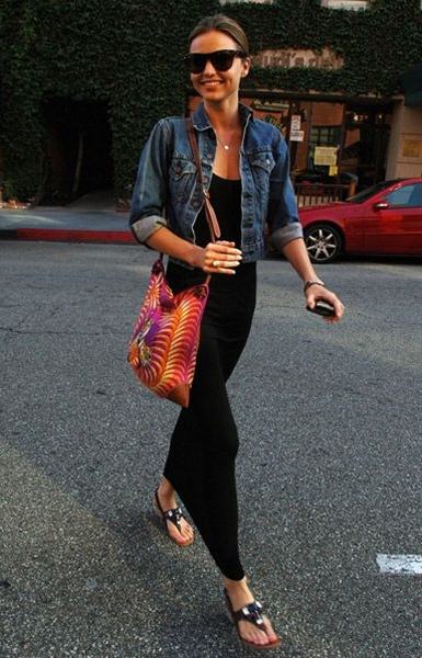 Shopping in Beverly Hills, wearing a black maxi dress, denim jacket, thong sandals and a swirly pattern bag.