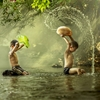 Thai boys splashing with in a river. by Jakkree Thampitakkul