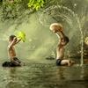 Thai boys splashing with in a river. by Jakkree Thampitakkul