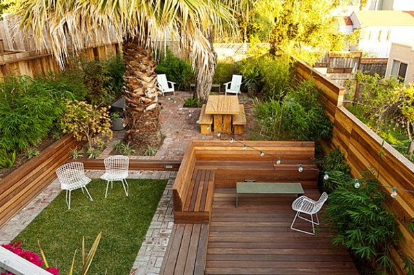 Another popular strategy for landscaping a small yard involves dividing it into sections and designing each of them with care. For example, the yard below from Growsgreen Landscape Design features patio space, deck space and a brick-framed green