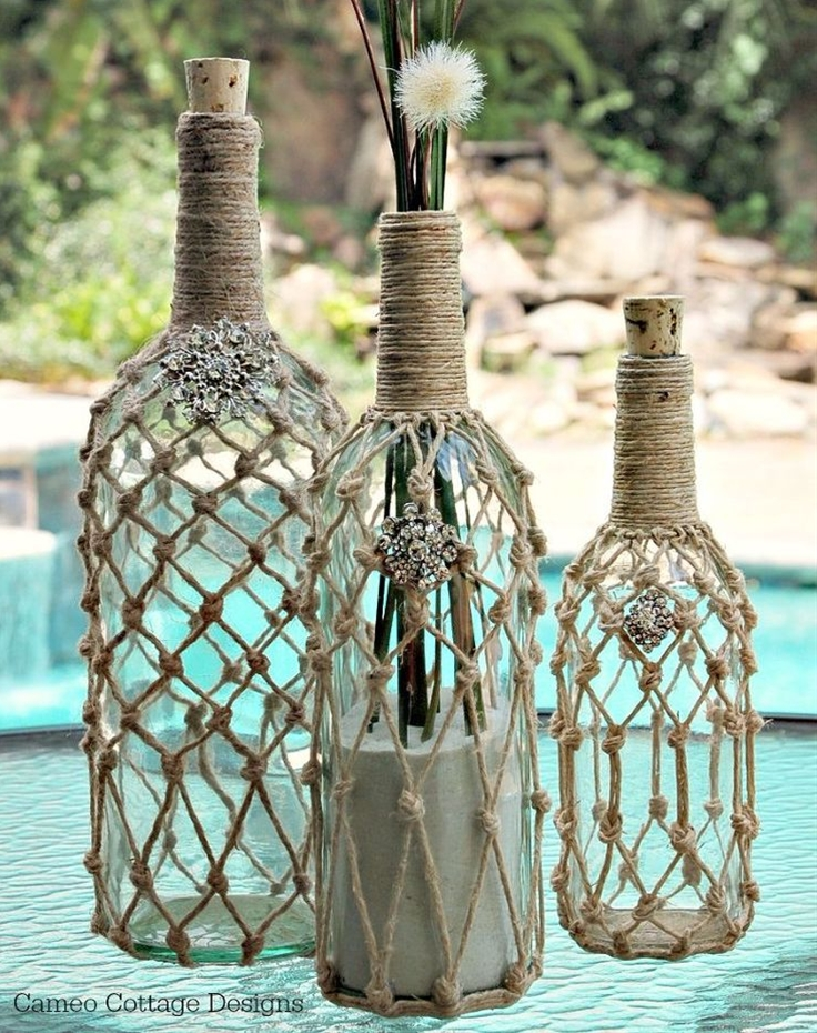 "I love recycling bottles- no idea why but there are many things you can do with them and uses for them too. These are going to be used in my beachy decor, with the hope of having a beach cottage home soon! I didn't have any real type demijohn bottles, which is just a large wine jug with a slender neck. I got the slender neck bottles and a couple of them are wine bottles so this works for me! I had everything on hand so there was no cost to me except a bag of play sand that I bought to photograph the bottles with to get a beachy look. I got some fun pretties by saving my trash! Hubby says the word is, ""hoarder!"" I say, ""he should be thankful I am!"""
