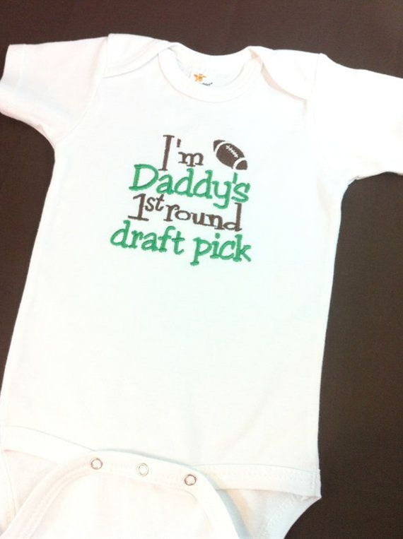 "Bodysuit is embroidered to read ""I'm Daddy's 1st Round Draft Pick"" in brown and green. Perfect for game day, or every day wear"