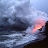 Glow of lava is reflected in steam plume at water's edge east of Kupapa'u Point. A littoral cone formed by spatter from steam explosions sits on top of the sea cliff to the right. 10 February 1988
