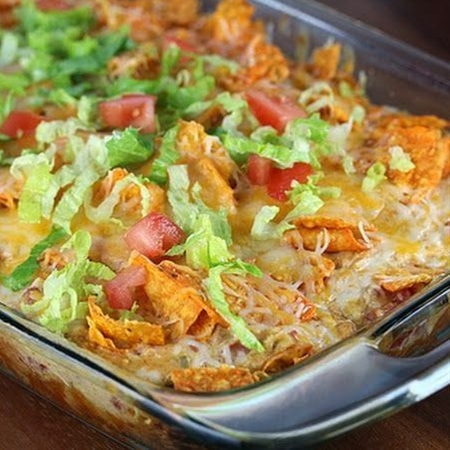 Ingredients: 2 cups shredded cooked chicken,  2 cups shredded Mexican cheese blend (divided),  1 (10 oz) can cream of chicken soup,  ½ cup milk,  ½ cup sour cream,  1 can Ro-tel tomatoes (drained),  ½ packet taco seasoning,  1 large bag Doritos,  Shredded lettuce (optional),  diced tomato (optional).