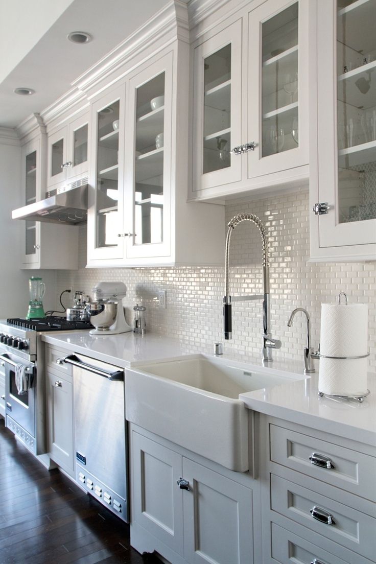 white kitchen cabinets, glass doors, dark wood floors. Backsplash - white mini subway tile