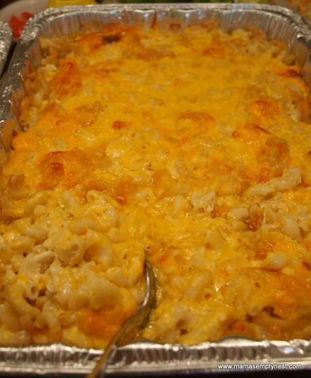 Ingredients: 1 pound elbow macaroni, 1 cup whole milk, 2 12-ounce cans evaporated milk, 3 eggs, 1 cup butter, cut into small pieces, ½ pound Colby cheese, grated, ½ pound Monterey Jack cheese, grated, ½ pound sharp Cheddar cheese, grated, 1 pound Velveeta cheese, cut into small chunks ½ cup sour cream, Salt, to taste,  1 TB white pepper,  1 TB sugar,  1 cup grated mild Cheddar cheese for the topping.
