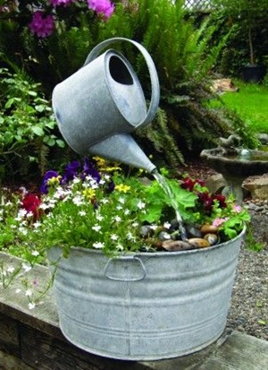 Watering beautiful plants growing in an old wash tub.....watering can hanging in midair over the flowers. I just love all things!!