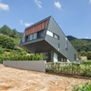 Unusual Zinc-Cladded Leaning House Disrupts Hillside Landscape