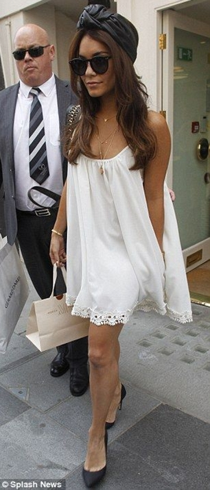 The actress looked chic in a flowing cream babydoll dress, a black leather turban and matching stilettos