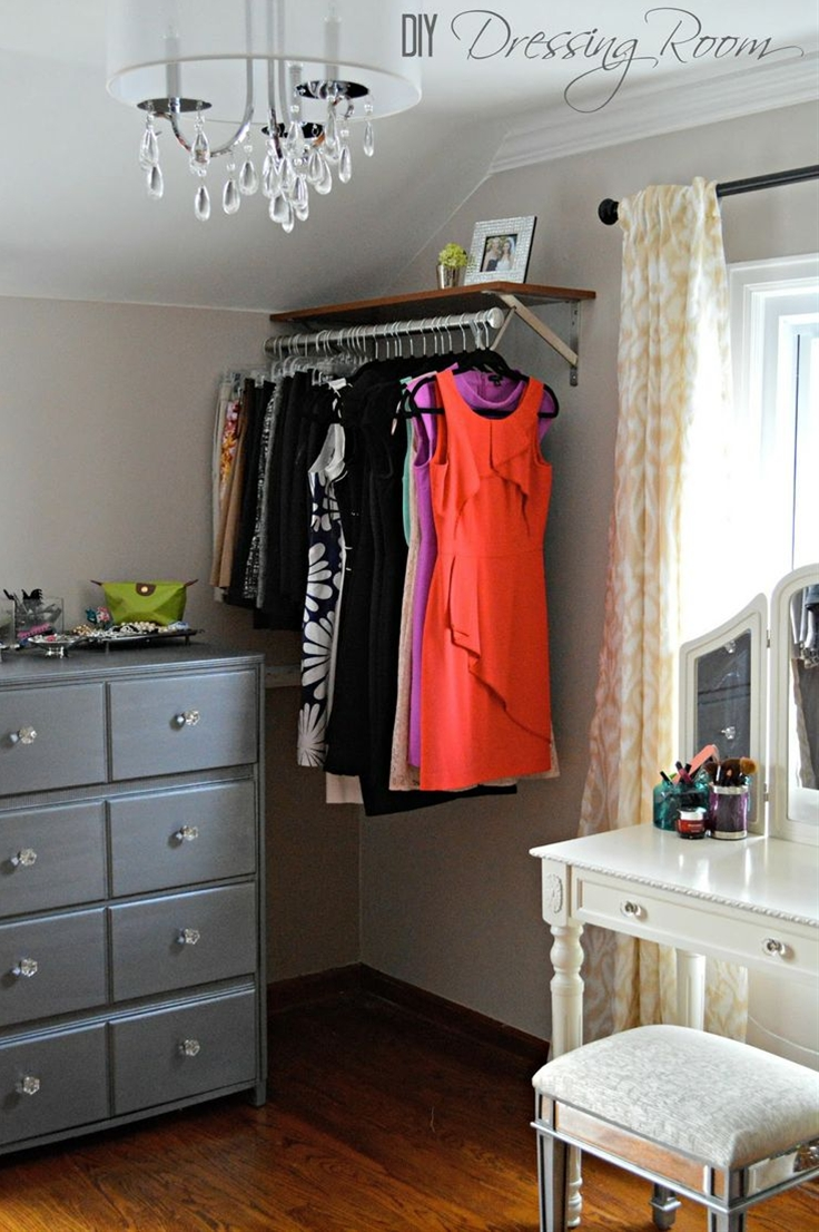 Check out this gorgeous converted bedroom makeover--- vanity in front of window, vintage lighting, garment racks, small dresser w/ vanity tray, build in laundry sorter
