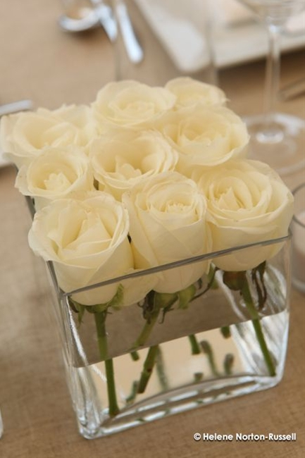 Dollar Store square vases with 9 white roses each. this will be gorgeous on those dark wine tablecloths you picked out.