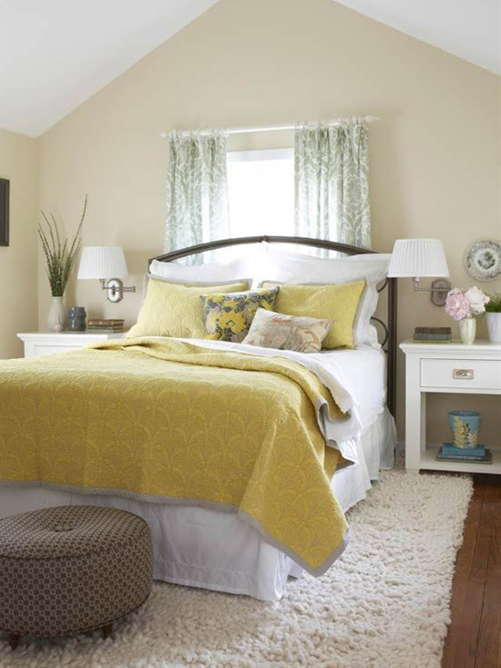 Canary yellow bedding gives this nearly neutral bedroom something to sing about. Beige walls, walnut flooring, and a patterned brown ottoman provide a neutral foundation that keeps the small space from feeling cramped.