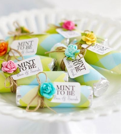 """Rolls of mints can be purchased in bulk, dressed up in lightweight patterned paper, and secured with adhesive. Use a digital die-cutting tool to mass-produce the """"Mint to Be"""" tags, and tie them on with twine. Adhere a pretty flower embellishment."""