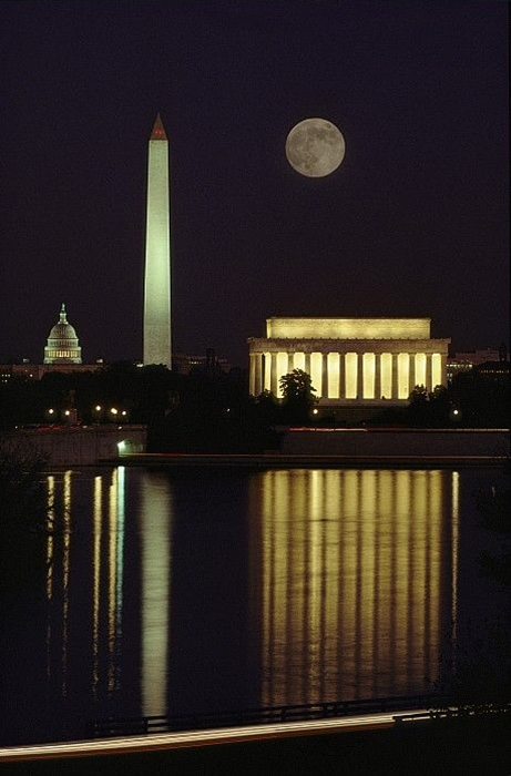 Moonrise over the Lincoln Memorial. The Washington Monument and Capitol dome a re seen in the background.