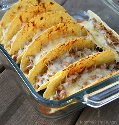 Ingredients: 2lbs ground beef, 4 teaspoons dried minced onion,  3 teaspoons chili powder,  1 teaspoon cornstarch,  1 teaspoon garlic powder,  1 teaspoon ground cumin,  ½ teaspoon dried oregano,  1/8 teaspoon cayenne pepper,  1 (8 ounce) can tomato sauce,  1 (16 ounce) can refried beans,  2 cups shredded Colby-jack cheese,  18-20 hard taco shells,  Optional Condiments-,  lettuce (shredded),  tomato (diced),  Salsa,  Guacamole.