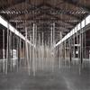 Wooden poles randomly strike the ground at Zimoun's installation in New York