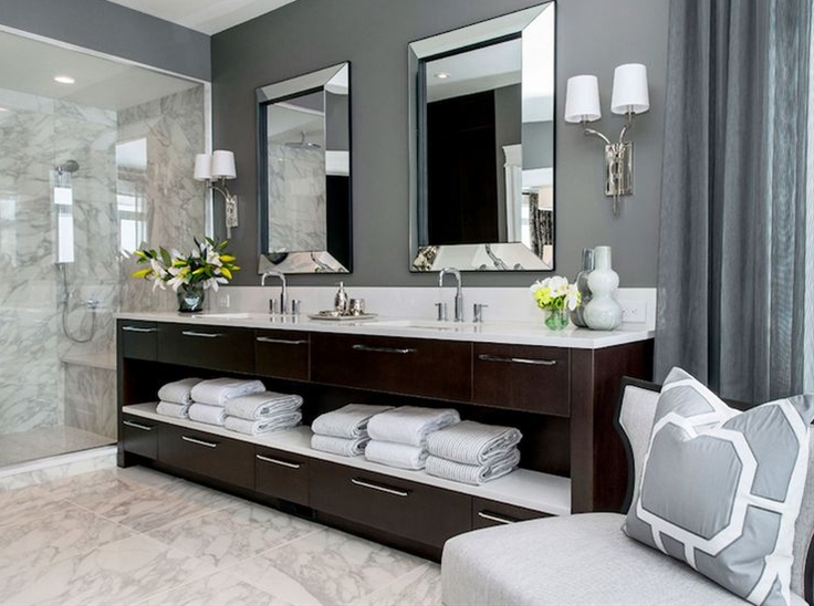 fabulous bathroom with dark gray walls pairing with gray drapes. The bathroom features a dark brown standing open vanity with lower and upper drawers and a middle shelf holding fresh bath towels. The dual vanity pairs with a white counter and undermount sinks with gooseneck faucets. A pair of mirror framed mirrors hangs over the vanity flanked by a pair of two arm polished nickel sconces. The walk-in shower beside the vanity includes built-in shower bench with marble tiled floors and surround. The bathroom floors are also tiled in marble. A gray accent chair topped with gray and white geometric pillow, stands in the corner of the space.