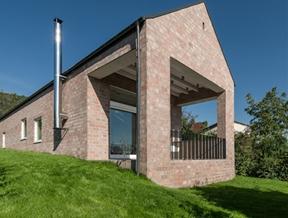 Long Brick House by Foldes Architects accommodates a 17-metre-long bookshelf
