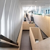 Multi-level wooden structure frames meeting areas in London office by Threefold Architects