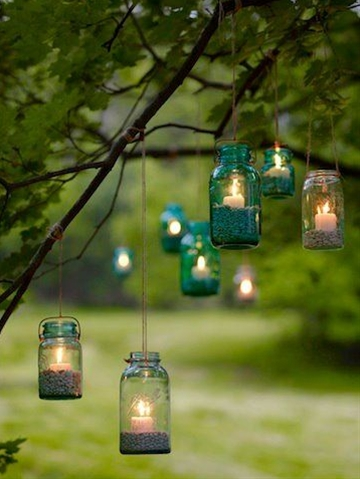 Fill clean canning jars with dried beans to hold the votive candles upright, then suspend with twine, tying them securely to branches. Hang the jars at various heights for a romantic, informal look.