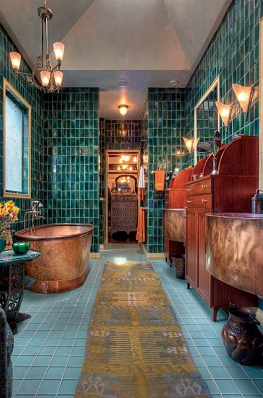 a copper soaking tub could almost be floating amid the watery setting of teal, green, and bronze tile. Kathryn designed the custom mahogany cabinetry and handmade copper sinks.