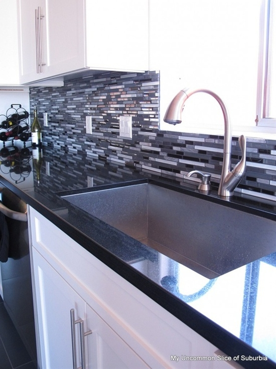 white cabinets and black counter tops are perfectly tied together with that amazing 50 shades of grey backsplash and stainless steel hardware/appliances. the natural light is a winner as well :)